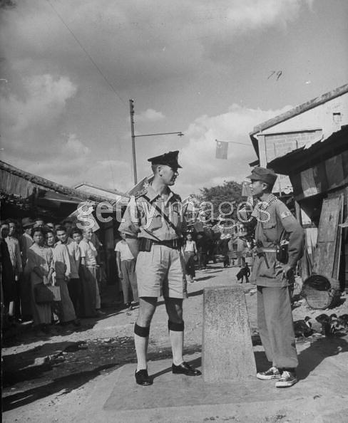British police inspector (L) standing on his half of the village while Red Chinese Army irregular standing on the right side of the border marker which divides the village. 1949 10 1