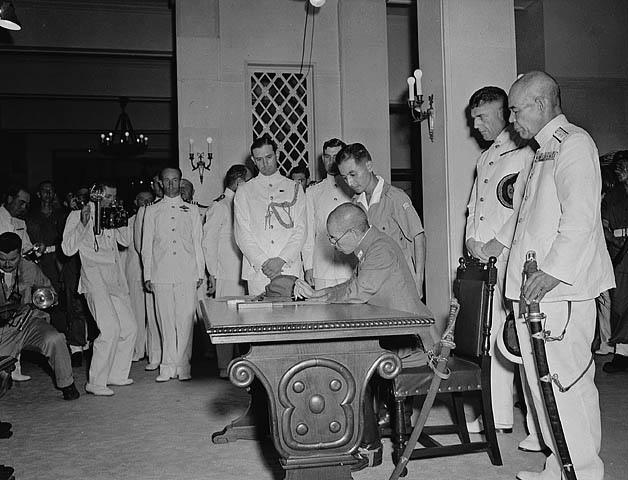 Lt.-Gen. Tanaka signs the Instrument of Surrender while Vice Admiral Fujita awaits his turn, Government House