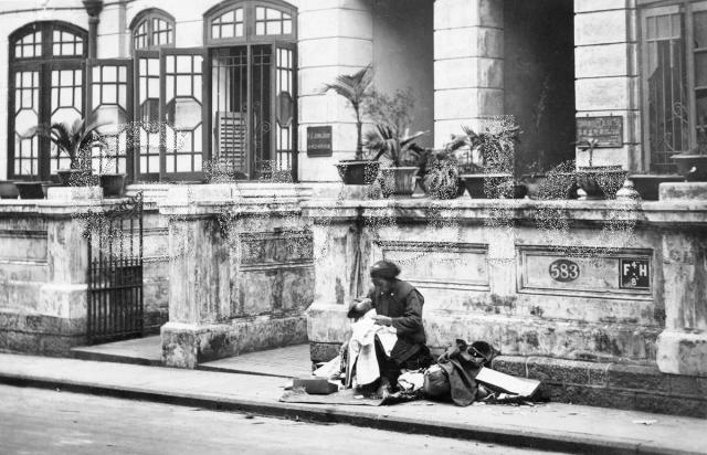 A Chinese woman sewing on Wyndham Street