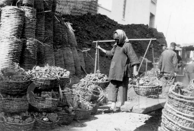 Woman carrying baskets of coal