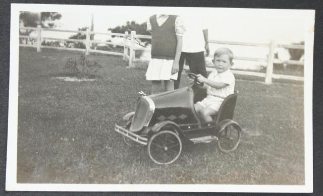 John Anton-Smith in pedal car on lawn by HKEC staff quarters