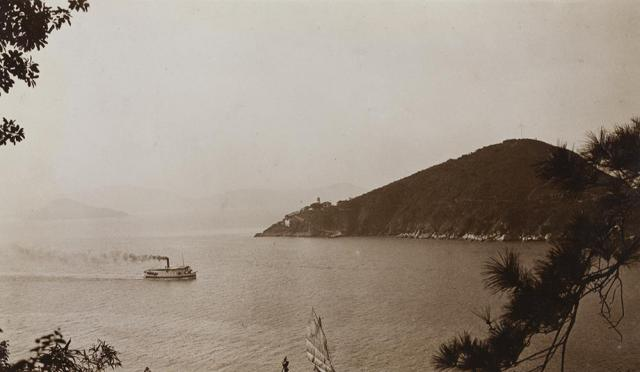 Green Island lighthouse, and a ferry boat in Sulphur Channel, Hong Kong