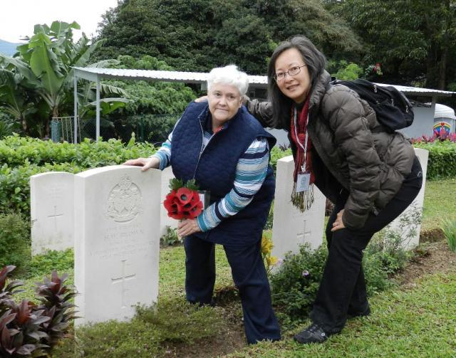 X. Rosemary places poppies at her uncle's grave.jpg