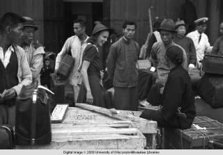 Hong Kong, an American evacuee with porters during World War II