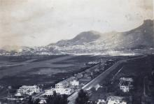 """View of camp with Kawloon City in the background"""