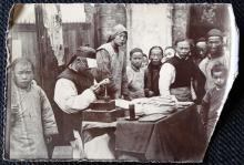 Chinese craftsman with a group of young spectators, ca. 1910
