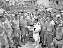 Cmdr. Peter MacRitchie of HMCS Prince Robert with liberated Canadian prisoners of war at Sham Shui Po Camp, Hong Kong