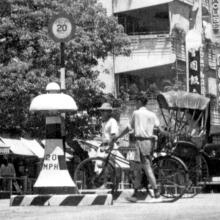 A cyclist and a rickshaw puller, waiting to cross Nathan Road at the junction with Austin Road in the 1950s
