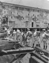 Landing platoon sending Chinese back across a damaged pier/bridge at Kowloon