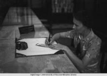 Hong Kong, an American evacuee signing a Travelers cheque during World War II