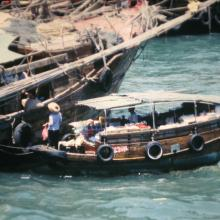 Fishing junk being provisioned from sampan
