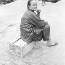 Hong Kong, woman sitting on a crate at a pier