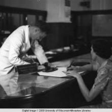 Hong Kong, an American evacuee writing a travelers cheque at the American Express Travel Department during World War II